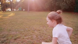 A cheerful little girl runs on a road in a park on a sunny summer day. Back view, slow mo