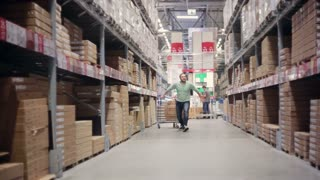 A cheerful man is happy about his shopping, hopping between shelves with goods in a warehouse