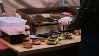 A chef in white gloves makes burgers. Man putting but on the top of hamburgers and skewers pierces each burger Back view