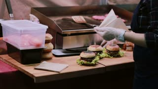 A chef in white gloves putting every burger into package for the customers to be handed over
