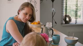 A close-up of a beautiful young mother and her daughter who is colouring at the kitchen table. Slow mo, Steadicam shot