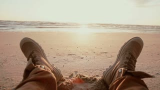 A close up of two feet in brown boots resting on a sandy beach at dawn.