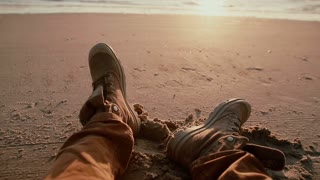 A close up of two worn boots that belong to a man resting on a sandy beach watching beautiful sunset.