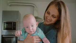 A close up of young mothers face while she is holding her adorable baby facing the camera. Slow mo, Steadicam shot