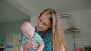 A close up of young mothers face while she is holding her adorable baby facing the camera. Slow motion