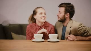 A couple in love having coffee, sitting on a sofa, talking to each other and happily smiling.