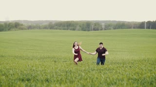 A couple in love running through a wheat field, holding hands, smiling, slow mo, steadicam shot