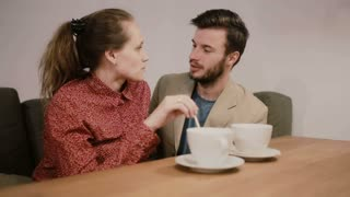 A couple in love sitting on a sofa at the table with empty coffee cups on it. They are talking and smiling, kissing.