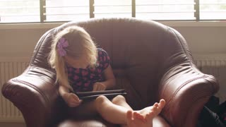 A cute blond little girl wearing all pink issitting on a chairand playing a game on tablet. 4k