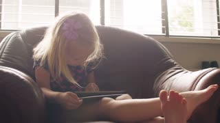 A cute blond little girl wearing all pink issitting on a chairand using tablet. 4k