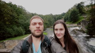 A cute couple is standing together on a wooden bridge over a waterfall posing for a selfie.