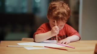 A cute little boy sitting at the table and drawing with the colored pencils on white paper.