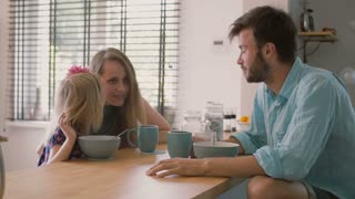 A cute little daughter is whispering something in her mothers ear during family breakfast. Slow mo