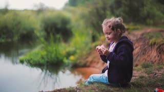A cute little girl is sitting on a river bank, eating watermelon. Blurred nature at the background. Side view