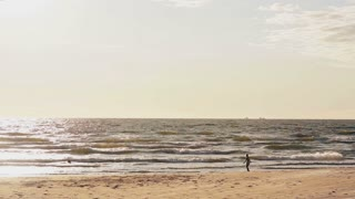 A distant view of a young girl who is standing on a sandy beach looking at foamy waves coming to her feet.