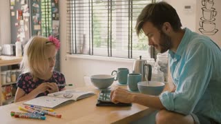 A father is working at his iPad while his daughter is colouring at the kitchen table. Slow mo