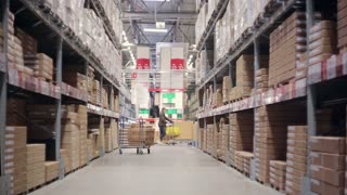 A funny man is surprised by a variety of goods walking between shelves of goods in a warehouse