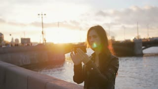 A girl taking selfie as the sun sets in a wonderful place. Busy road, a bridge, a river at the background, slow mo