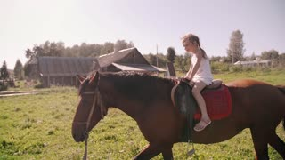 A happy little girl riding a horse in the nature on a sunny day. She is smiling, having fun. Slow mo