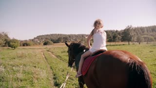 A happy little girl riding a horse in the nature on a sunny day. She is smiling. Slow mo, back view