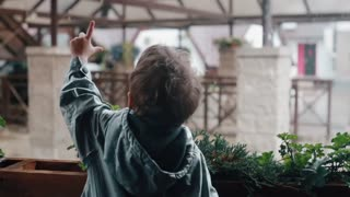 A little boy points at rain drops falling from sky and roofs. Fence with plants, architecture. Slow mo, back view
