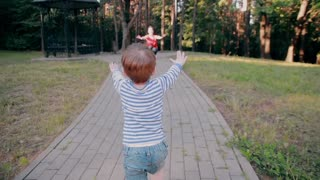 A little boy walks on a road in a park with his arms risen and tenderly hugs his mom. Slow mo, back view
