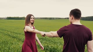 A man and a woman are joining hands, walking in a field, hugging and kissing. Slow mo, steadicam shot.