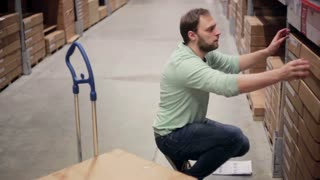 A man in a blue sweater is taking boxes from the shelf, putting them on the trolley in a storage warehouse