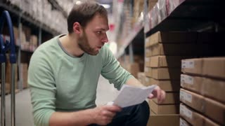 A man is looking for necessary packages, taking them from the shelf with cardboard boxes in a warehouse