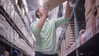 A man is putting boxes back on the shelves in a warehouse and going away from the camera