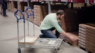 A man is taking a box from the shelf, putting it on the trolley, checking his list in a storage warehouse