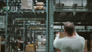 A man is taking boxes from the shelves, taking them and goes away through shelves in a warehouse. Back view. 4K