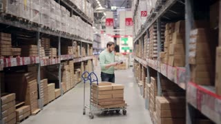 A man standing with a trolley with boxes on it, is checking his list and looking for necessary things in a warehouse
