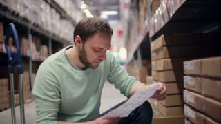 A man with a beard in a blue sweater checking his list in a warehouse