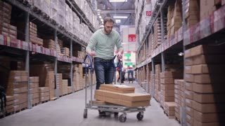 A man with a trolley in a warehouse. He is checking his list and taking necessary boxes