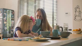 A mother looks at her daughters colouring with a smile and then starts talking to her husband. Slow mo, Steadicam shot