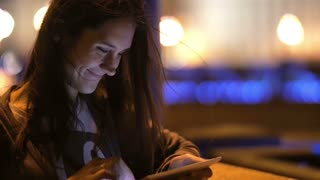 A pretty young woman using her tablet at night. She smiles, wind blows her hair, blurred background, slow mo