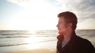 A side view of a young dark-haired man in a black coat who is standing at the sea shore enjoying the sunset