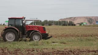 A side view of an agricultural tractor, plowing a field for sowing. Birds are flying and landing on the field.