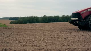 A side view of an agricultural tractor, plowing a field, soil dust. close-up