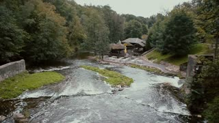 A view from the top on a beautiful mountain river coming down to a cute wooden building creating stunning waterfalls