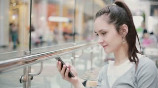 A view of a girl from a side angle. She is sitting in a public place, using her phone, smiling.