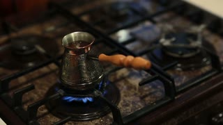 A view of coffee in a coffee pot with a long handle preparing on fire.