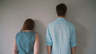 A woman and a tall man are standing near the wall their backs facing the camera.
