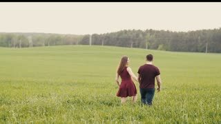 A young beautiful couple in love happily walking through long grass, holding hands. Slow mo