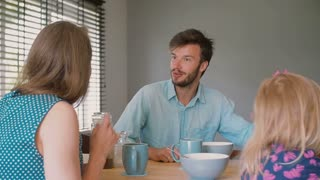 A young dark-haired father is having a conversation with his beautiful wife at the kitchen table. Slow motion