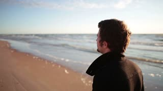 A young dark-haired man in a black coat is walking along the sea shore.