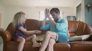 A young father and cute happy little daughter are playing pat-a-cake on the sofa in the living room. Slow motion
