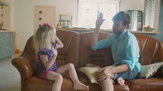 A young father and his cute happy little daughter are giving each other high fives sitting on the sofa. Slow motion