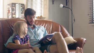A young father and his happy little blond daughter are reading a story on leather sofa in the dining room. 4K